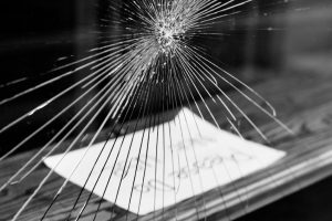 "Shattered glass, shop window. A message ""Please do not use"" is visible, out of focus."