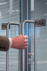 close up of a hand pulling open an office door